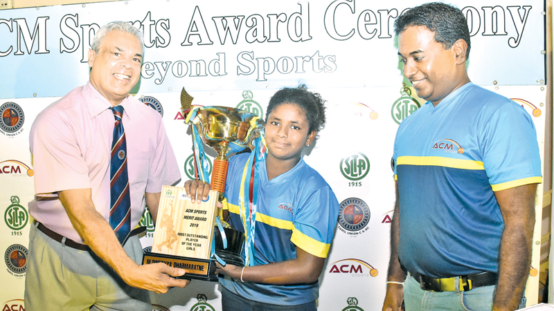 Girls' Most Outstanding Player Dinethya Dharmaratne receiving the trophy from the chief guest Nihal Wijewickrema