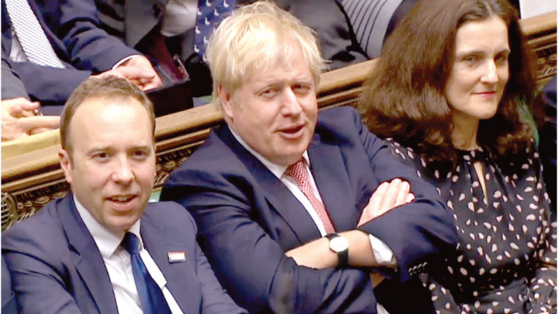 Britain's Prime Minister Boris Johnson (C) reacting after his Government won the vote on the third reading of the European Union (Withdrawal Agreement) Bill, in the House of Commons in London on January 9, 2020. - AFP