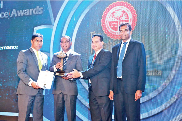 Nanda Fernando, Managing Director, Sampath Bank PLC (Second from left) and Tharaka Ranwala, Senior DGM Consumer Banking (Left) accepting the 'Winner of Excellence in Corporate Governance' award