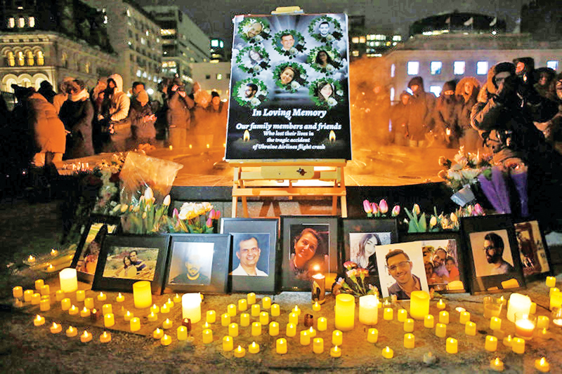An altar with photographs of the victims who were killed in a plane crash in Iran is seen as people gather around to held a vigil in their memories on January 9, 2020 in Ottawa, Canada.