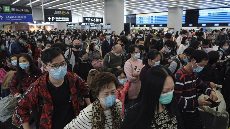 Passengers wear protective face masks at the departure hall of the high-speed train station in Hong Kong.