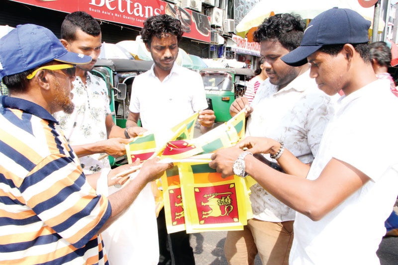 Patriotic fervour grips Sri Lankans across the globe as the country celebrates the 72nd Independence Day at Independence Square today. Picture shows vendors selling national flags in Colombo ahead of nationwide celebrations. Picture by Nissanka Wijeratne
