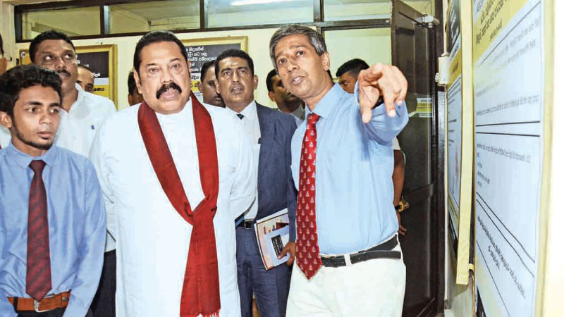 Prime Minister Mahinda Rajapaksa at the exhibition to showcase a National Economic Policy at the office of the Organisation of Professional Associations (OPA) on Monday. Ports, Shipping and Highways Minister Johnston Fernando and Government Medical Officers' Association President Dr. Anuruddha Padeniya were also present. Picture by Wimal Karunathilaka