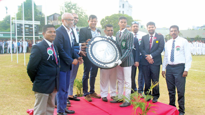 Victorious Angora House captain M.N.M. Rinaz receiving the challenge shield from the chief guest, Julian Bolling.