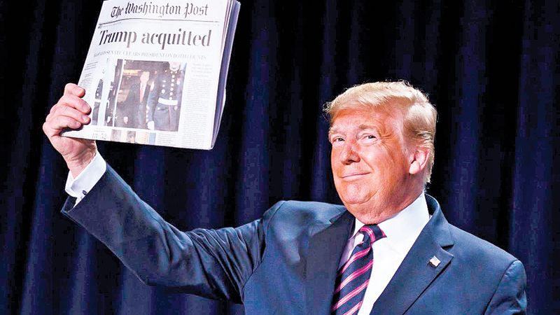 "US President Donald Trump holds up a newspaper with the headline that reads ""ACQUITTED"" at the 68th annual National Prayer Breakfast, at the Washington Hilton on Thursday."