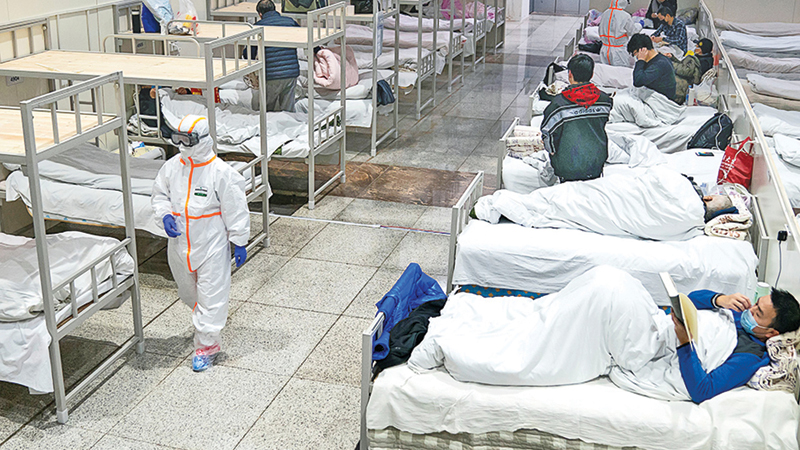 Medical workers in protective suits attend to patients at the Wuhan International Conference and Exhibition Center, which has been converted into a makeshift hospital to receive patients with mild symptoms caused by the novel coronavirus.