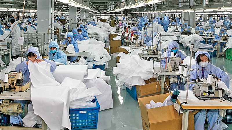Workers producing protective clothing at a factory in Wuxi, in China's eastern Jiangsu province. - The factory, which previously produced suits and sportswear, switched to production of protective clothing as demand increases due to the ongoing coronavirus outbreak. - AFP