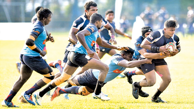 Police Sports Club's Shan Akila powers his way past two Air Force defenders in their Dialog 'A' Division League Rugby Match played at Police Park yesterday which Police won 29/12. Picture by Samantha Weerasiri