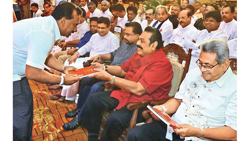 State Minister Mahindananda Aluthgamage presenting his book to Prime Minister Mahinda Rajapaksa while President Gotabaya Rajapaksa and Minister Wimal Weerawansa look on. Picture by Prime Minister's Media.