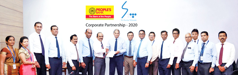 Sujeewa Rajapakse Chairman, People's Bank and Rohan Fernando Chairman, SLT exchanges the MoU, other officials of People's Bank and SLT look on.