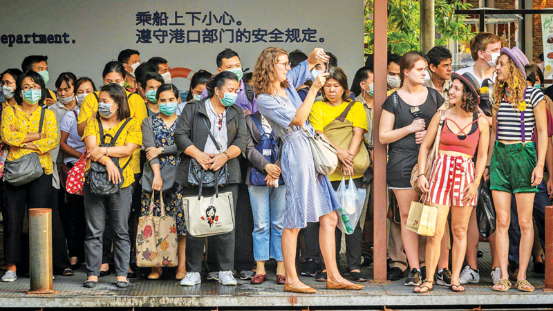Tourists take pictures next to commuters with facemasks, worn amid fears of the spread of the COVID-19 novel coronavirus, as they wait for a canal boat in Bangkok on Monday. - AFP