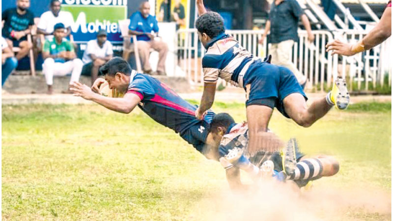 The Josephian defence tries vainly to stop Kingswood from scoring a try in their Dialog schools rugby match played at Havelock Park yesterday.