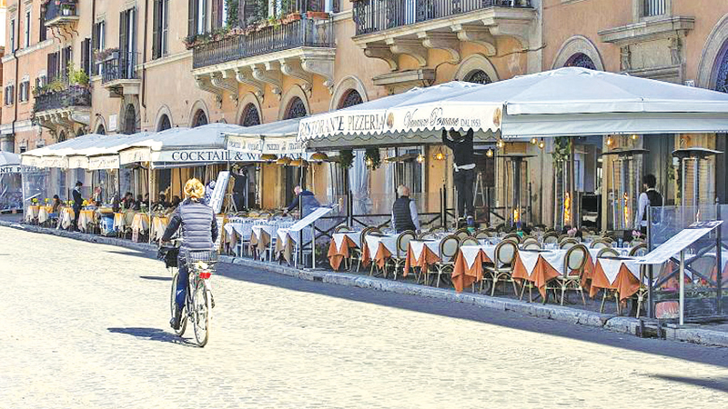 A woman cycles down an empty street and closed eateries  in downtown Rome. The Italian government is set to close cinemas and theatres, and ban public events across the country to try to contain the COVID-19 outbreak.