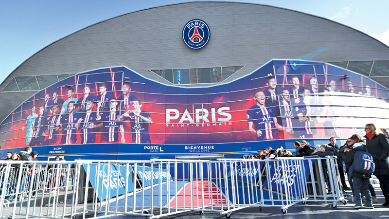 People stand next to barriers set up to prevent contact between players and supporters amid fear of Covid-19 (novel Coronavirus) at the Parc des Princes stadium in Paris before the Ligue 1 football match between Paris Saint-Germain and Dijon. – AFP