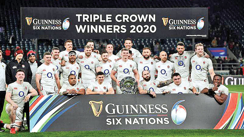 England players celebrate winning the match as they pose with the triple crown.