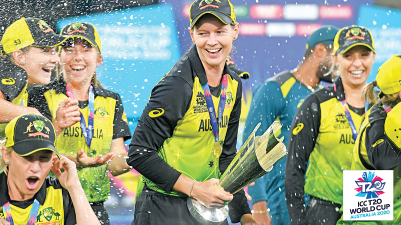 Australia's captain Meg Lanning (C) holds the trophy as she celebrates with the teammates after winning the Twenty20 women's cricket World Cup final against India in Melbourne on Sunday. - AFP