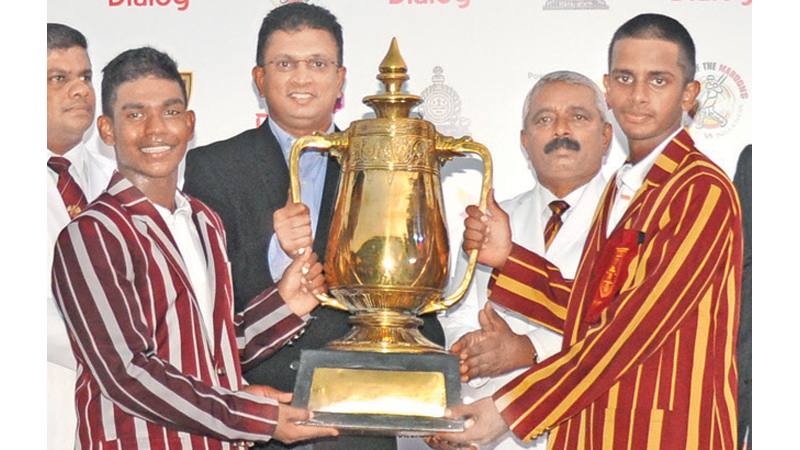 Nalanda College captain Avishka Perera and Ananda College skipper Kanishka Ranthilakage receive the Dr. N M Perera Memorial Challenge Trophy from Supun Weerasinghe, Director/Chief Executive, Dialog Axiata PLC after the 91st encounter ended in a draw at the SSC.