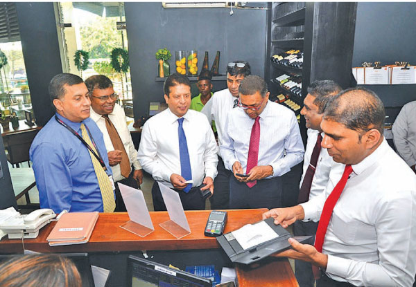 "DFCC Bank CEO Lakshman Silva performs first DFCC Pay Transaction at Sugar Bistro"".  Denver Lewis Head of Card Centre DFCC Bank (first from left), Gemunu Gunasumana Assistant Vice President Card Operations DFCC Bank(second from left), Nishan Weerasooriya Head of IT DFCC Bank (fourth from the left), Thimal Perera DCEO DFCC Bank (Third from right) , Viraj Mudalige Group Director / Chief Executive at Epic Lanka (second from right), Chrishan Jayamanne Manager Merchant Acquiring Cards and Virtual Wallets DFCC Ban"