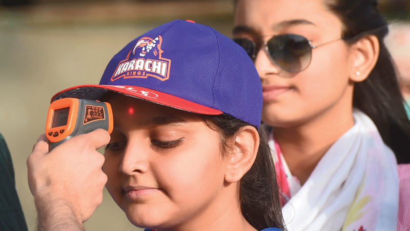 A health official checks the body temperature of a cricket fan amid concerns of the spread of the COVID-19 coronavirus at the entrance of the National Cricket Stadium in Karachi on Thursday before  a Pakistan Super League match. - AFP