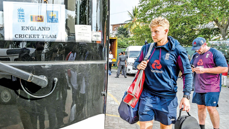England's captain Joe Root (L) boards the bus after the Test series against Sri Lanka was postponed at the P. Sara Oval Cricket Stadium yesterday due to the mounting coronavirus pandemic. - AFP