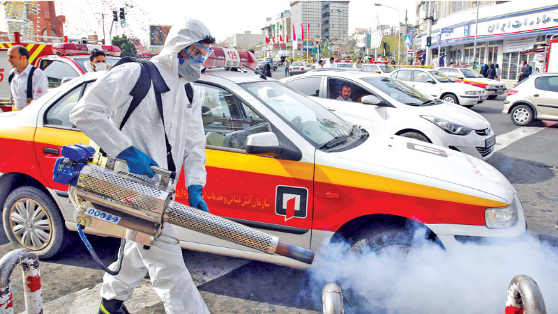 An Iranian firefighter disinfects a street in the capital Tehran in a bid to halt the wild spread of the COVID-19 coronavirus. – AFP