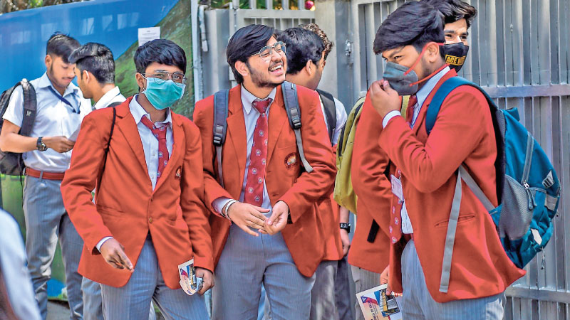 Students wearing facemasks amid concerns over the spread of COVID-19 novel coronavirus come out of a school after giving their board exam in New Delhi yesterday. - AFP