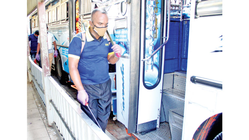 Disinfectants being sprayed to sanitize buses at the Central Bus Stand in Pettah, Colombo on Monday. Picture by Wimal Karunathilaka