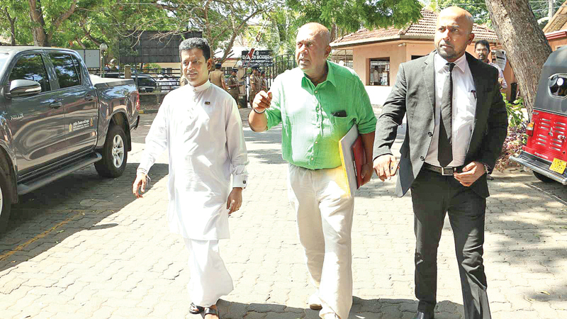 Former Finance Minister Mangala Samaraweera and former Deputy Minister Buddika Pathirana on their way to hand over the SJB nominations yesterday.