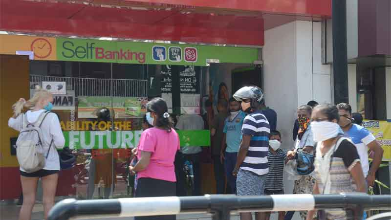 People stand apart from each other at an ATM Kiosk in Ambalangoda yesterday. Picture by Wimal Karunathilaka