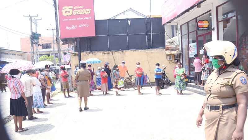 People form an orderly queue at a Sathosa outlet in Ambalangoda