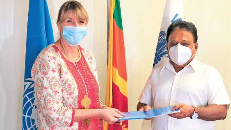 Brenda Barton, Country Director, WFP handing the letter to Dullas Alahapperuma, Minister of Education and Sports, confirming funds to supply take-home ration packages.