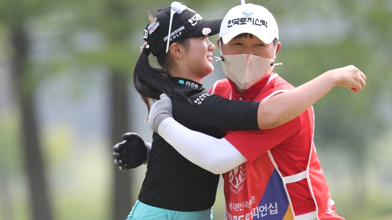 An emotional Park Hyun-kyung is hugged by her father who was caddying for her.