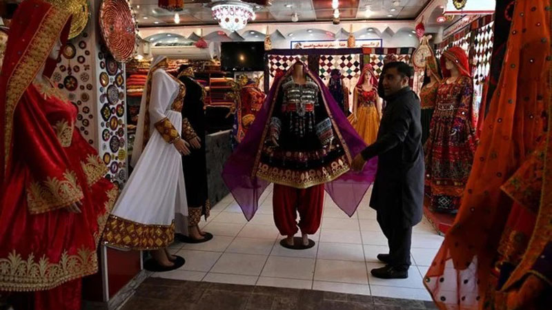 A shopkeeper displays a dress on a mannequin as he waits for customers during the government-imposed lockdown as a preventive measure against the coronavirus in Kabul, Afghanistan on Tuesday.  - AFP