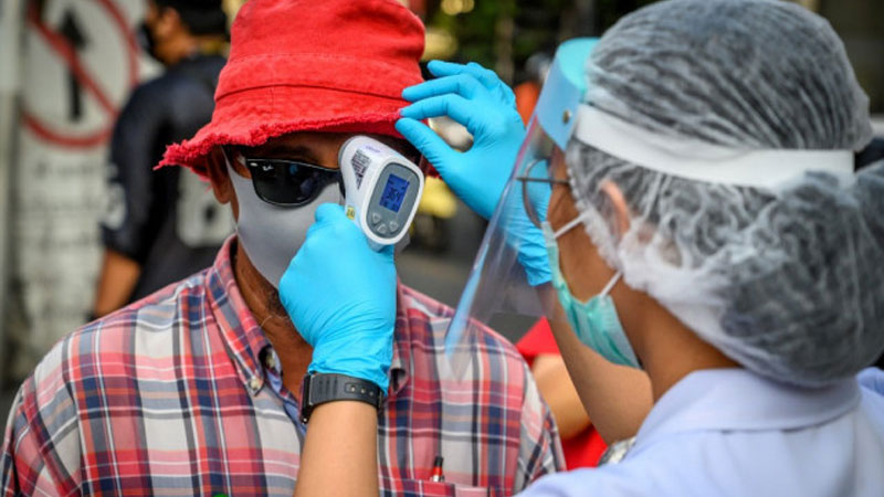 A nurse checks the temperature of a pro-democracy protester before a gathering to commemorate the 10th anniversary of the Red Shirt anti-government protests in Bangkok on May 19, 2020. - AFP