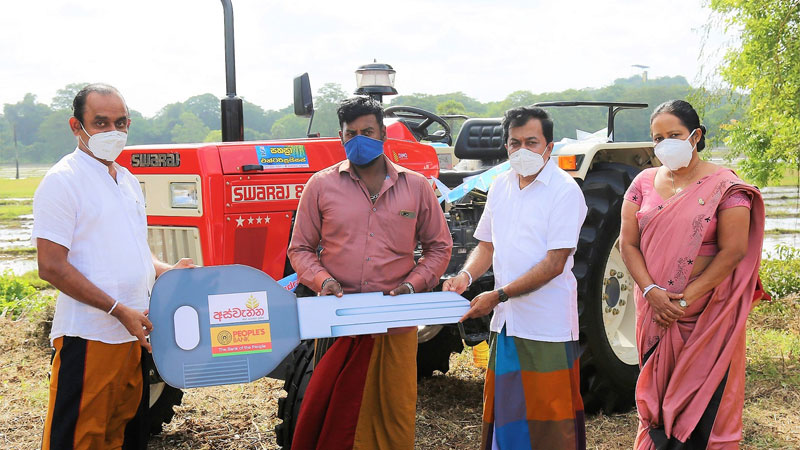 People's Bank Chairman - Sujeewa Rajapakse giving away a loan grant under the Aswenna loan scheme to purchase a tractor. Acting CEO/ General Manager - Boniface Silva Anuradhapura Regional Manager Chandrika Nissanka are also in the capture.