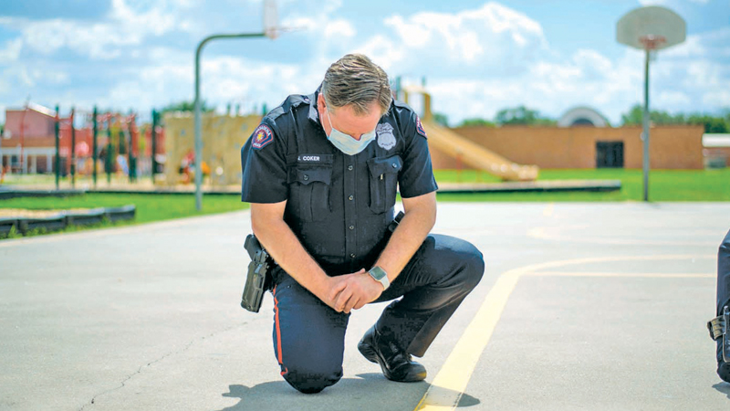 """A Police officer takes a knee during a 9 minute moment of silence in honour of George Floyd during a  """"Sit In Protest"""" to mourn the death of Floyd at DeepWater Park in Pasadena, Texas on Sunday. - AFP"""