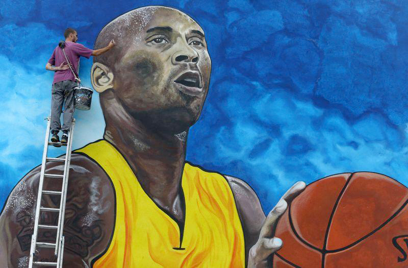 Artist Deni Bozic (27) paints the last details on his tribute mural honoring former Los Angeles Lakers basketball star Kobe Bryant on a school building wall in Gradiska, Bosnia and Herzegovina Monday.