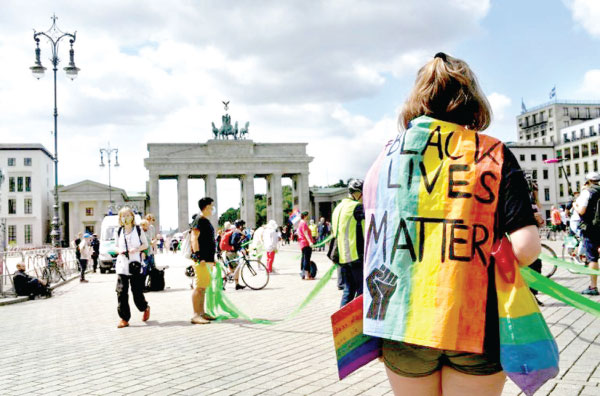 """Protesters  take part in a demonstration organised by the """"#unteilbar"""" (indivisible) movement in front of the Brandenburg Gate in Berlin."""