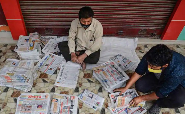 Vendors arrange different vernacular newspapers before delivering it to customers during the nationwide lockdown amid the coronavirus pandemic, at Ganeshguri in Guwahati. - PTI