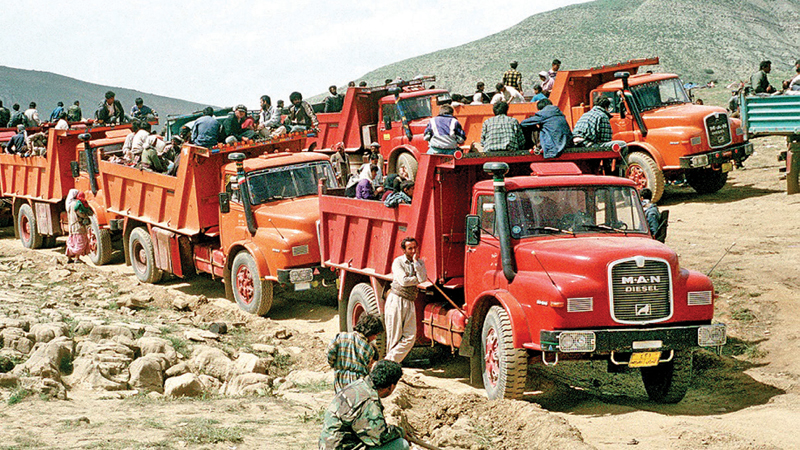 Kurdish refugees travel by truck between their mountain campsites and tent cities established by military personnel.