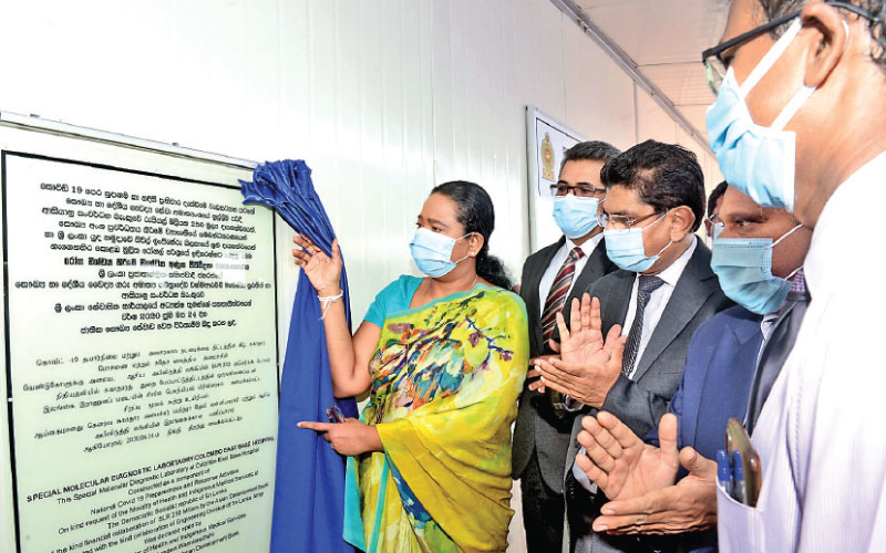 Health Minister Pavithra Vanniarachchi opening the molecular diagnostics laboratory, while Health Ministry Secretary Major General Sanjeewa Munasinghe, Health Services Director-General Dr. Anil Jasinghe, and other officials look on.