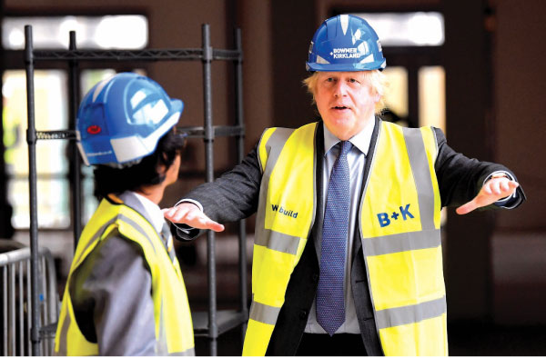 Britain's Prime Minister Boris Johnson talks with year-ten pupil Vedant Jitesh when he visited the construction site at Ealing Fields High School in west London on Monday. - AFP