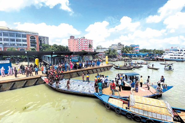 Rescue workers bring bodies of victims after a ferry capsized at the Sadarghat ferry terminal in Dhaka on Monday.
