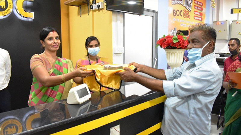 Chief Guest EP Assistant General Manager Kumudini Yogaratnam receives the first cash deposit from a customer