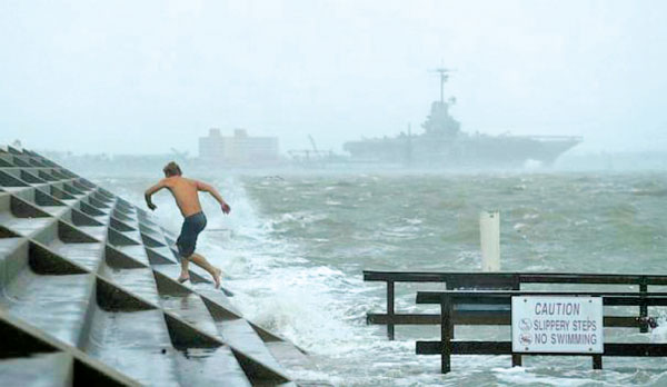 A man jumps from a wave as Hurricane Hanna made landfall in Corpus Christi, Texas on Saturday.
