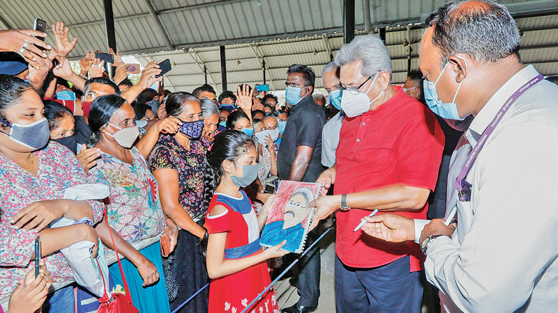 President Gotabaya Rajapaksa who attended a public meeting at the Horana fair premises to support the Kalutara District Sri Lanka Podujana Peramuna General Election candidates being presented a drawing of himself by a young girl. Picture courtesy President's Media Division