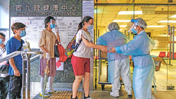 Residents are given free COVID-19 coronavirus test kits by workers (R) at a government clinic in the Kowloon-side Sham Shui Po district of Hong Kong as part of a city-wide testing initiative on Tuesday. - AFP