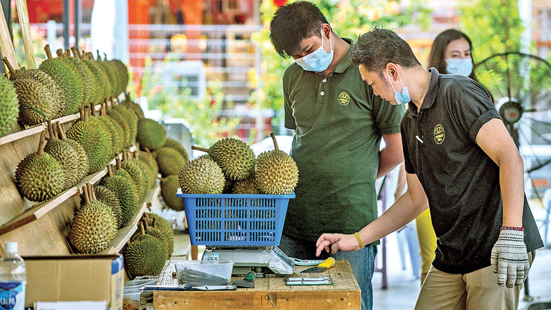 A worker using a calculator at a durian shop in Kuala Lumpur. When a coronavirus lockdown confined Malaysians to their homes, street traders selling durians moved their pungent produce online -- and have been enjoying an unexpected spike in demand. - AFP