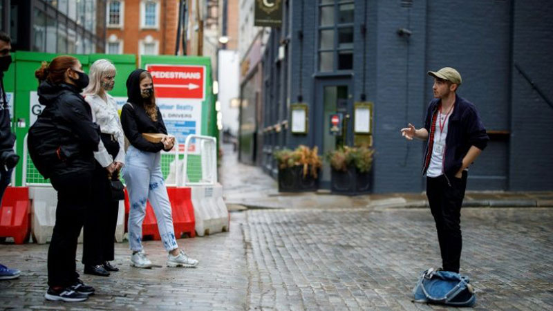 A tour guide explains a point to visitors as social distancing and travel restrictions have cut down the number of people taking tours of London.