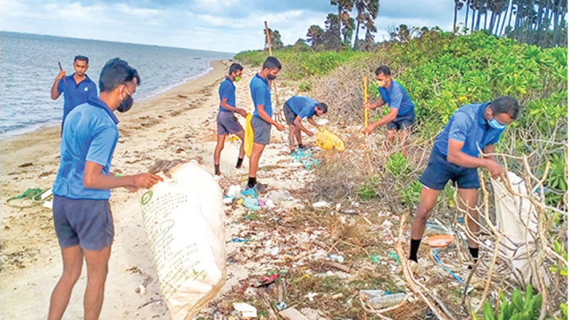Naval personnel cleaning the coast.